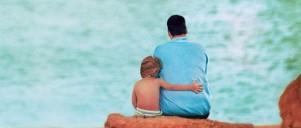 Lille dreng og hans far kigger ud over havet