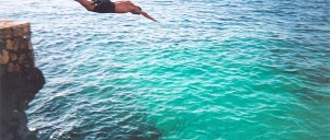 Mand springer i vandet fra klippe